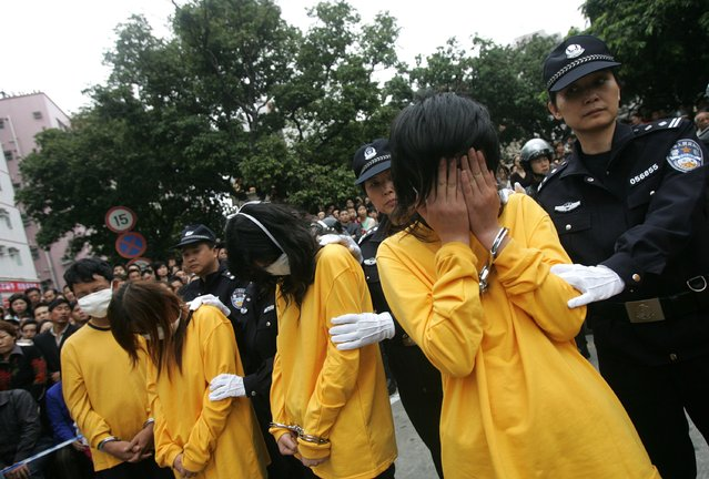 SHENZHEN, CHINA - NOVEMBER 29: (CHINA OUT) Suspected criminals accused of dealing with s*x service including prostitution and organizing prostitution, cover their faces during a public sentence on November 29, 2006 in Shenzhen of Guangdong Province, China. The local authorities have launched a campaign to crack down on prostitution business. According to state media, male and female prostitution are widespread despite being illegal in China.  (Photo by China Photos/Getty Images)