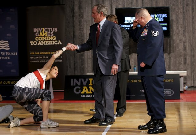 Former U.S. President George W. Bush helps wounded veteran Kristen Esget, U.S. Coast Guard Yeoman 3rd Class, to her feet before a demonstration of sitting volleyball while meeting wounded veteran competitors who are training for the Invictus Games Orlando 2016 at the Intrepid Sea, Air & Space Museum in New York, December 3, 2015. The Invictus Games will bring together more than 500 competitors from 15 nations to compete in 10 sports. At right is U.S. Air Force Technical Sergeant Israel Del Toro. (Photo by Mike Segar/Reuters)