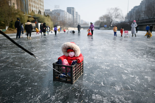 A man (not in picture) pulls a child sitting in a box on a frozen river in Beijing on January 22, 2021. (Photo by Wang Zhao/AFP Photo)