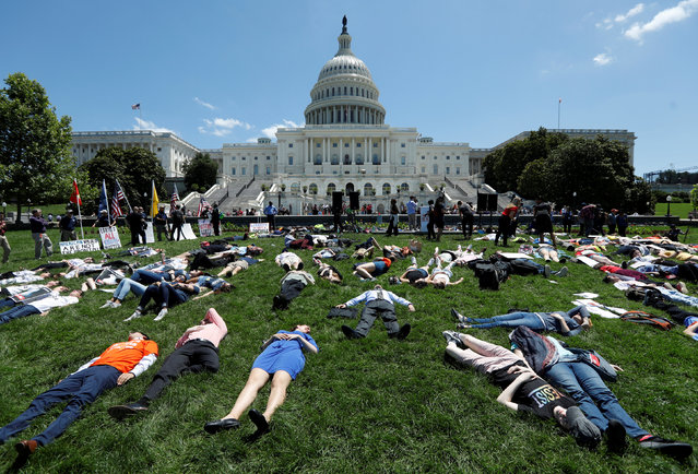 Activists mark the second anniversary of the Pulse Nightclub shooting where a gunman killed 49 people in Orlando with a die-in at the U.S. Capitol in Washington, U.S., June 12, 2018. (Photo by Kevin Lamarque/Reuters)