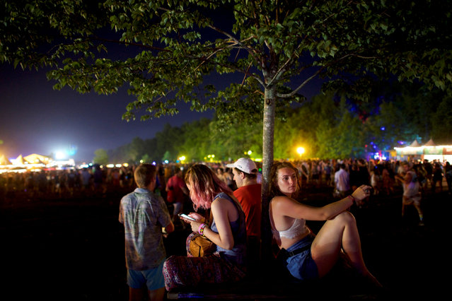Grace Kennedy, 19, rests against a tree while others use their smartphones on the third day of the Firefly Music Festival in Dover, Delaware U.S., June 16, 2018. (Photo by Mark Makela/Reuters)