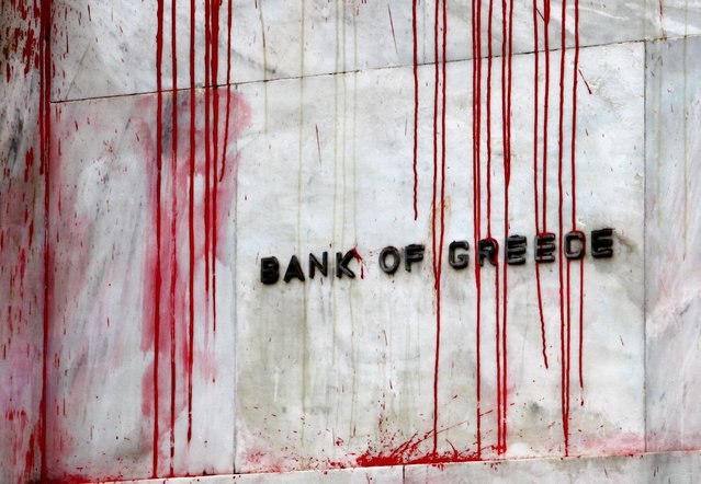 A branch of the Bank of Greece is seen stained with red paint thrown by demonstrators during a protest in central Athens, in this December 6, 2010 file photo. (Photo by Yannis Behrakis/Reuters)