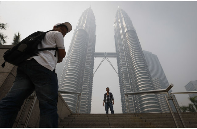A tourist poses for a photo in front of  Malaysia's landmark Petronas Twin Towers obscured in haze in Kuala Lumpur, Malaysia, Monday, June 24, 2013. Malaysian authorities declared a state of emergency Sunday in a southern district where a smoky haze blamed on Indonesian forest fires has triggered one of the country's worst pollution levels in years. (Photo by Vincent Thian/AP Photo)