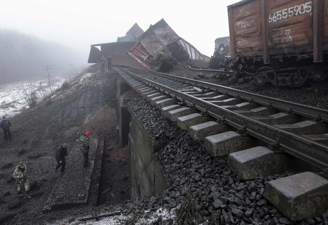 Emergency workers inspect a damaged bridge near Kuznetsovka village in Zaporizhzhya region January 21, 2015. An overnight blast destroyed a railway bridge in the eastern Ukrainian region of Zaporozhye, cutting a railway link between the city of Mariupol and Ukraine's west. Ukraine's state security service said suspects had been identified in relation to the blast, and were currently being searched for. (Photo by Reuters/Stringer)