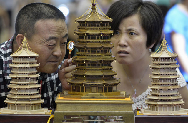 A visitor uses a magnifying glass to look at a handmade wood carving in the shape of a Chinese ancient pavilion at a culture industry exhibition in Taiyuan, Shanxi province July 2, 2013. (Photo by Jon Woo/Reuters)