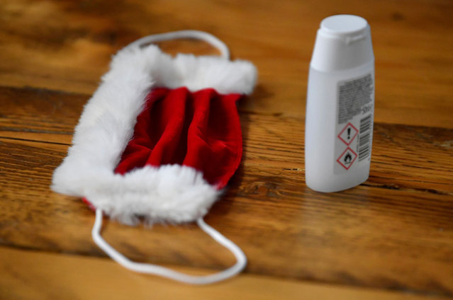 A face mask and hand sanitiser are seen on a desk as students take part in a training session at the Ministry of Fun Santa School, as it develops an online app for children to speak with Santa during the Christmas season, as the continuation of the coronavirus disease (COVID-19) pandemic means most in-person Santa's Grotto experiences will have to be cancelled, London, Britain, November 10, 2020. (Photo by Toby Melville/Reuters)