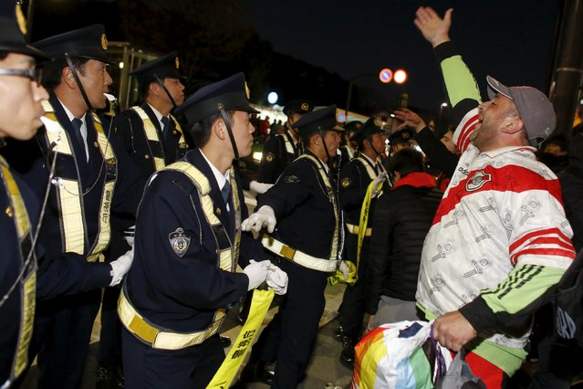 Police try to control supporters of Argentine club River Plate as they briefly occupy a pedestrian crossing in central Tokyo after a pre-match party in Tokyo's Yoyogi park, ahead of their team's Club World Cup final soccer match against Barcelona, Japan, December 19, 2015. (Photo by Thomas Peter/Reuters)