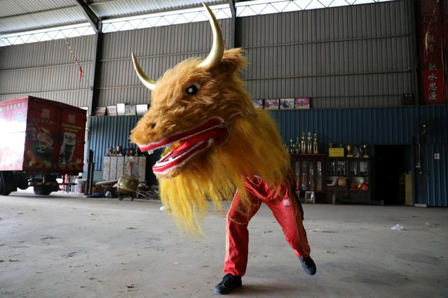 A member of Kun Seng Keng Lion and Dragon Dance Association, demonstrates a dance with an ox mask designed for Lunar New Year at a training centre, during an interview with Reuters, in Muar, Malaysia on February 5, 2021. (Photo by Lim Huey Teng/Reuters)