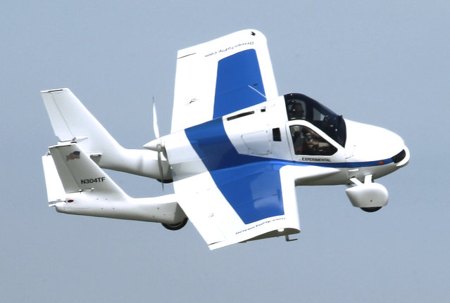 The Terrafugia Transition roadable aircraft, which has been displayed as a development prototype  for several years, flies during the airshow Monday, July 29, 2013 at the Experimental Aircraft Association's AirVenture in Oshkosh, Wis.  It is also a street legal road car. The week-long convention, which started today, attracts more than 10,000 planes, thousands of pilots and aviation enthusiasts as well as companies and entrepreneurs unveiling the latest technology. (Photo by Mark Hoffman)