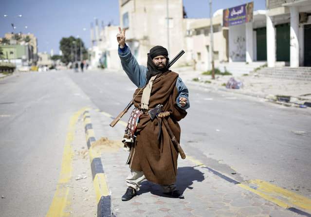 An armed resident gestures a victory sign in the main square in Zawiya, 30 miles (50 kilometers) west of Tripoli, in Libya, Sunday, February 27, 2011. (Photo by Ben Curtis/AP Photo)