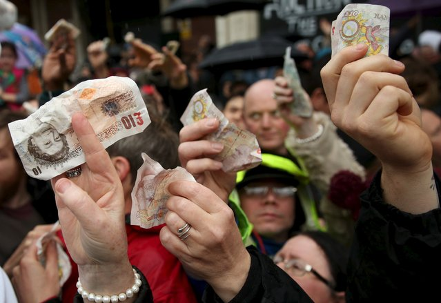 People hold out money as butchers sell their remaining produce of the year at discounted prices during the traditional Christmas Eve auction at Smithfield's market in London December 24, 2015. (Photo by Neil Hall/Reuters)
