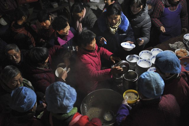 Residents queue up for Laba porridge provided by a temple in Hefei, Anhui province January 27, 2015. Tuesday marks the Laba Festival, which falls on the eighth day of the twelfth month of the Chinese Lunar calendar and commemorates the date of Sakyamuni Buddha's enlightenment. The tradition of eating Laba porridge on this day is believed to bring good fortune to people. (Photo by Reuters/Stringer)