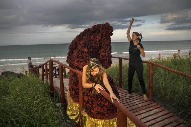 In this November 21, 2015 photo, Camila Lopez Rivas, 14, poses for portraits on a beach in Havana, Cuba, as an assistant lifts the train of her dress to make it look like its flying in the wind. Camila lives in Miami, the daughter of a truck driver who left Cuba when she was a baby. She doesn't remember the island, but wanted to return for the photographs and videos that Latin American girls typically take for their 15th birthdays. (Photo by Ramon Espinosa/AP Photo)