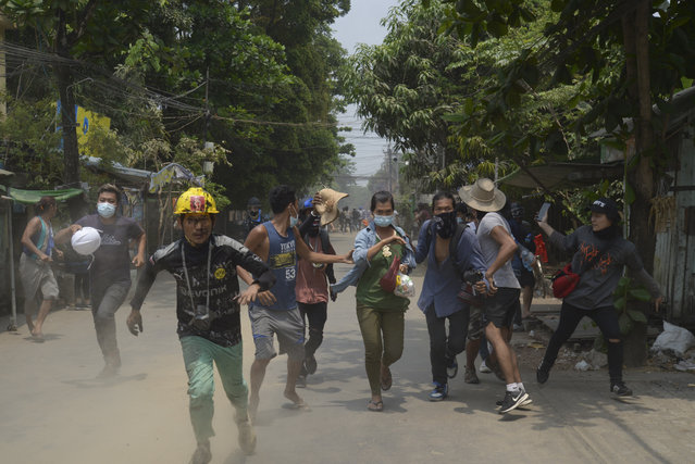 Anti-coup protesters run to avoid the military during a demonstration in Yangon, Myanmar on Tuesday March 30, 2021. (Photo by AP Photo/Stringer)