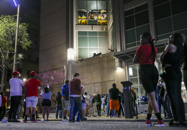 Onlookers watch from the street as inmates chant and throw things from broken windows at the St. Louis Justice Center, known as the city jail, on Sunday, April 4, 2021. (Photo by Colter Peterson/St. Louis Post-Dispatch via AP Photo)