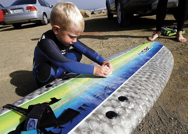 Triston waxes his surfboard before hitting the waves. (Photo by Joe Johnston/The Tribune of San Luis Obispo)
