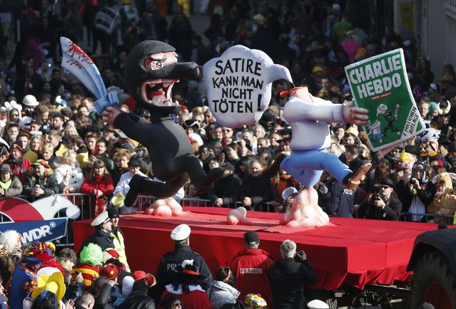 "A carnival float with a papier-mache caricature drives past revellers during the traditional Rose Monday carnival parade in the western German city of Duesseldorf February 16, 2015. Words read: ""You can't kill satire"". (Photo by Ina Fassbender/Reuters)"