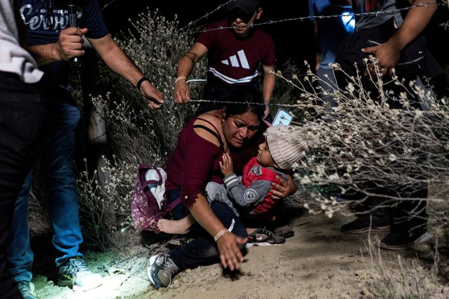 Asylum-seeking migrants' families go under a barbed wire fence while being escorted by a local church group to the location where they turn themselves in to the U.S. Border Patrol, after crossing the Rio Grande river into the United States from Mexico, in Roma, Texas, U.S. April 16, 2021. (Photo by Go Nakamura/Reuters)