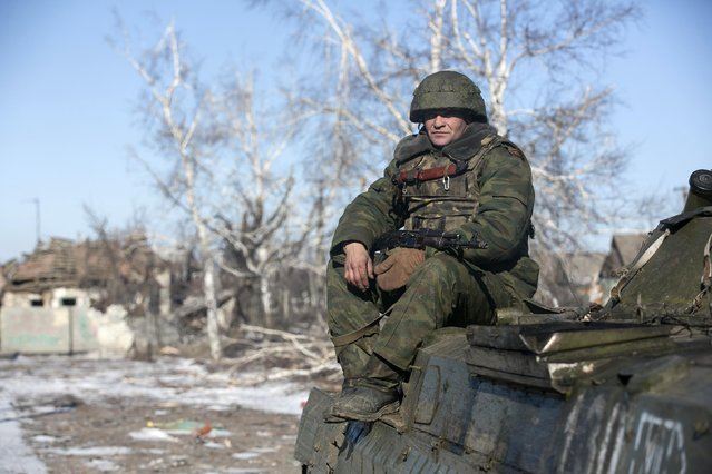 A fighter with separatist self-proclaimed Donetsk People's Republic army sits on top of an armoured personnel carrier in the village of Nikishine, south east of Debaltseve February 17, 2015. (Photo by Baz Ratner/Reuters)