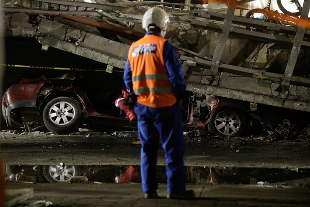 A rescue worker stands in front of a car trapped under an overpass for a metro that partially collapsed with train cars on it at Olivos station in Mexico City, Mexico, May 4, 2021. (Photo by Luis Cortes/Reuters)