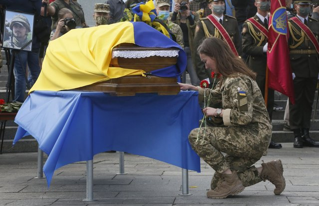 In this July 14, 2020, file photo, a Ukrainian soldier pays her final respects at the coffin of serviceman Taras Matviiv, honored with the Hero of Ukraine highest state award after being killed while fighting against pro-Russian rebels, during his funeral in Independence Square, Kyiv, Ukraine. Tensions have risen in the conflict in eastern Ukraine, with growing violations of a cease-fire and a massive Russian military buildup on its side of the border. (Photo by Efrem Lukatsky/AP Photo/File)