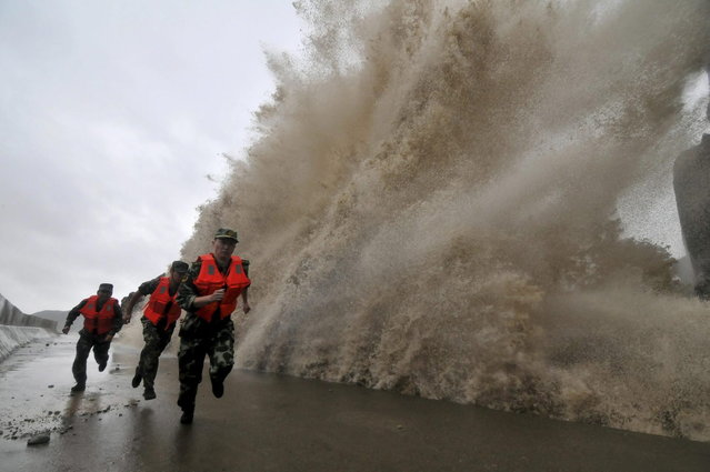 Frontier soldiers run as a storm surge hits the coastline under the influence of Typhoon Fitow in Wenling, Zhejiang province, October 6, 2013. China issued a red alert ahead of Typhoon Fitow, which is expected to lash east of the country on Sunday evening. (Photo by Reuters/China Daily)
