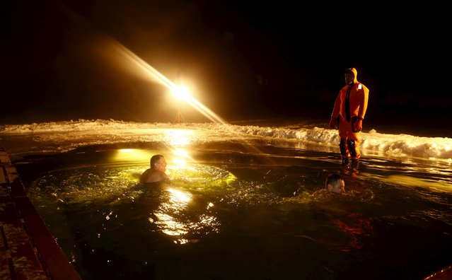 Men swim in the icy waters of a lake as part of celebrations for Orthodox Epiphany on the outskirts of Minsk, January 18, 2016. (Photo by Vasily Fedosenko/Reuters)