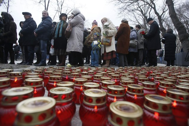 Lit candles are placed on the ground as people gather to attend a memorial service before the funeral of Russian leading opposition figure Boris Nemtsov in Moscow, March 3, 2015. Several hundred Russians, many carrying red carnations, queued on Tuesday to pay their respects to Boris Nemtsov, the Kremlin critic whose murder last week showed the hazards of speaking out against Russian President Vladimir Putin. REUTERS/Maxim Shemetov