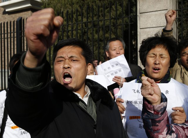 Family members of passengers aboard missing Malaysia Airlines flight MH370 shout slogans during a gathering outside the Malaysian embassy in Beijing March 8, 2015. Malaysian and Chinese officials say they are committed to the search for MH370 and in assisting families who are still waiting for concrete information on what happened to their loved ones a year ago.
