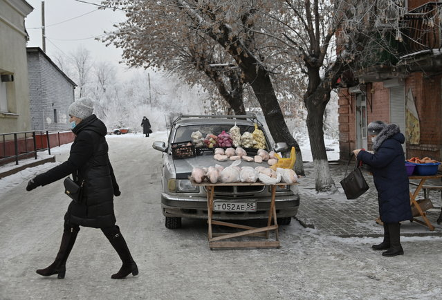 People wearing protective face masks amid the coronavirus disease (COVID-19) outbreak are seen near foodstuffs, which are displayed for sale on a car in Omsk, Russia on December 4, 2020. (Photo by Alexey Malgavko/Reuters)