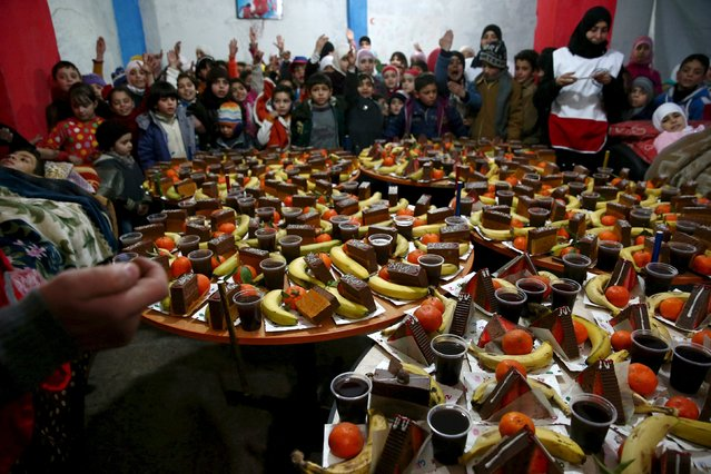 Children wait to be served with goodies during a party for children affected by war and in need for psychological support, in the Douma neighborhood of Damascus, Syria January 24, 2016. The party was organized by the Syrian Arab Red Crescent. Picture taken January 24, 2016. (Photo by Bassam Khabieh/Reuters)