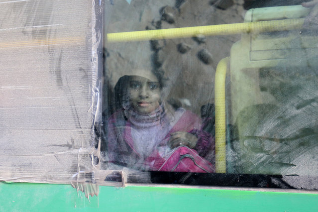 A girl rides a bus to be evacuated from a rebel-held sector of eastern Aleppo, Syria December 18, 2016. Picture taken December 18, 2016. The reflection on the window shows a damaged building. (Photo by Abdalrhman Ismail/Reuters)