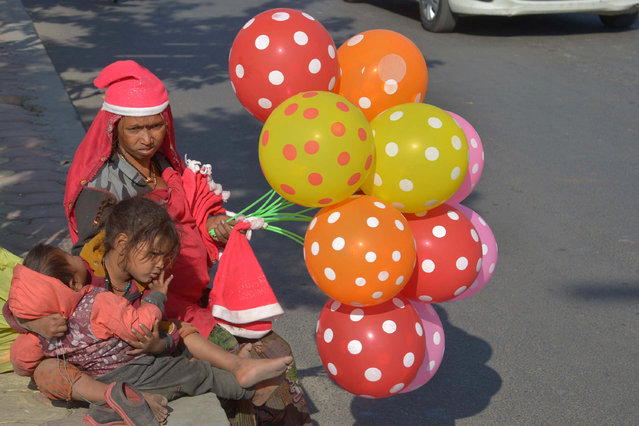Indian vendor Geeta sits on the side of the road with her two children as she sells Santa Claus hats and balloons at the roadside in Amritsar on December 21, 2016. lthough Indian Christians make up a mere two percent of the country's billion plus population, Christmas has become a popular festival in the Indian calendar. (Photo by Narinder Nanu/AFP Photo)