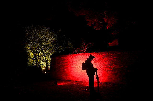 A figure of a World War I soldier is seen as buildings and trees are seen illuminated as part of the annual Winter Wonderland trail at Syon Park in west London on November 19, 2018. (Photo by Toby Melville/Reuters)