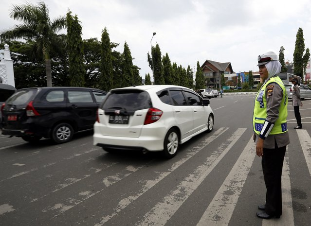 An Acehnese female police officer wear a hijab on duty in the street in Banda Aceh, Indonesia, 27 March 2015. (Photo by Hotli Simanjuntak/EPA)