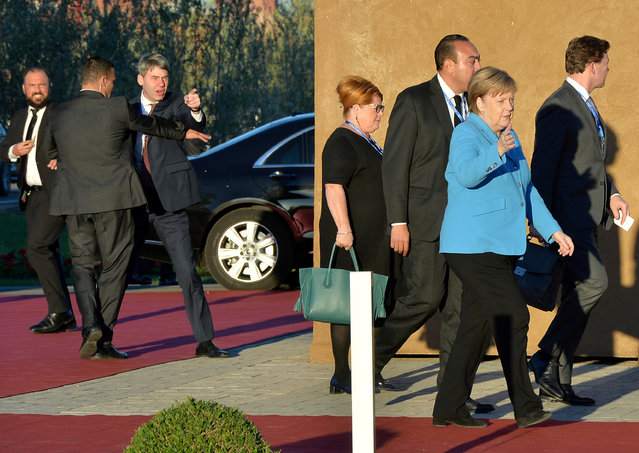 A man gestures as German Chancellor Angela Merkel arrives to the Intergovernmental Conference to Adopt the Global Compact for Safe, Orderly and Regular Migration, in Marrakesh, Morocco on December 10, 2018. (Photo by Abderrahmane Mokhtari/Reuters)