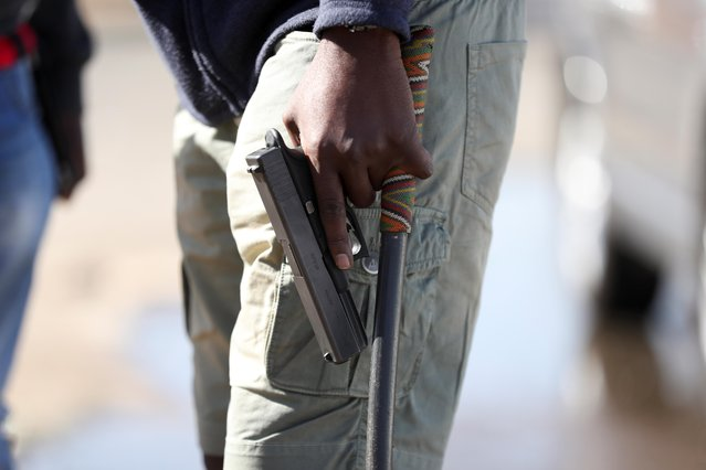 A man holds a pistol as the country deploys army to quell unrest linked to the jailing of former South African President Jacob Zuma, in Vosloorus, South Africa, July 14, 2021. (Photo by Siphiwe Sibeko/Reuters)
