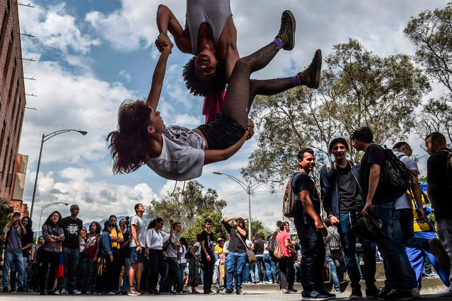University students demonstrate against the crisis in the public education, budget cuts and a tax reform project announced by the government of Ivan Duque in Medellin, Colombia on December 13, 2018. (Photo by Joaquín Sarmiento/AFP Photo)