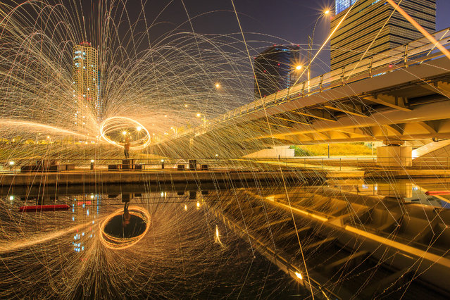 """Playing with fire"". Playing with fire beside the canal in the modern city. Songdo, South Korea. Photo location: Songdo, Incheon, South Korea. (Photo and caption by Sungjin Kim/National Geographic Photo Contest)"