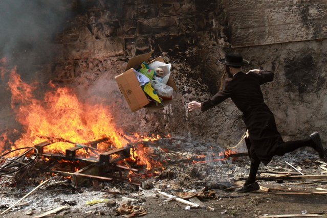 An Ultra-Orthodox Jew throws leavened items onto a fire in Jerusalem during the final preparations before the start of the Jewish Passover holiday, which begins at sunset, on April 3, 2015. (Photo by Gil Cohen Magen/AFP Photo)