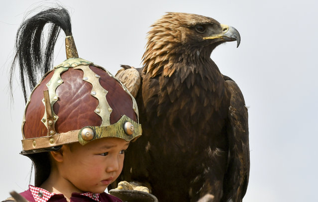 A Kyrgyz boy holds a golden eagle for an eagle hunt during the Third Nomad Games, in Cholpon-Ata, 250 kilometers (156 miles) of Bishkek, Kyrgyzstan on September 6, 2018,. The Central Asian nation of Kyrgyzstan held its biennial Nomad Games to promote and celebrate traditional sports of nomadic people. The week-long competition, which is held in a gorge near the picturesque Lake Issyk-Kul, feature traditional sports of nomad peoples such as horseback wrestling and goat polo. (Photo by Vladimir Voronin/AP Photo)