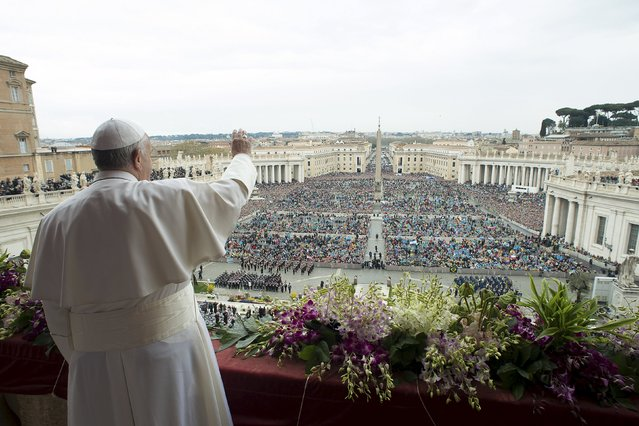 """Pope Francis waves as he delivers a """"Urbi et Orbi"""" message from the balcony overlooking St. Peter's Square at the Vatican April 5, 2015. (Photo by Osservatore Romano/Reuters)"""