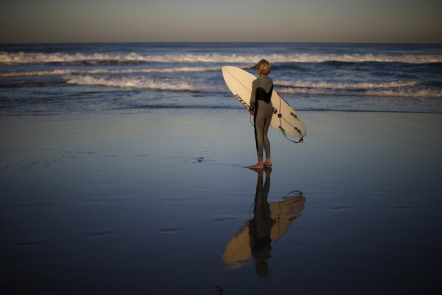 Carlos Price Gracida, 13, looks at the ocean after surfing at sunrise in Hermosa Beach, California March 24, 2015. (Photo by Lucy Nicholson/Reuters)