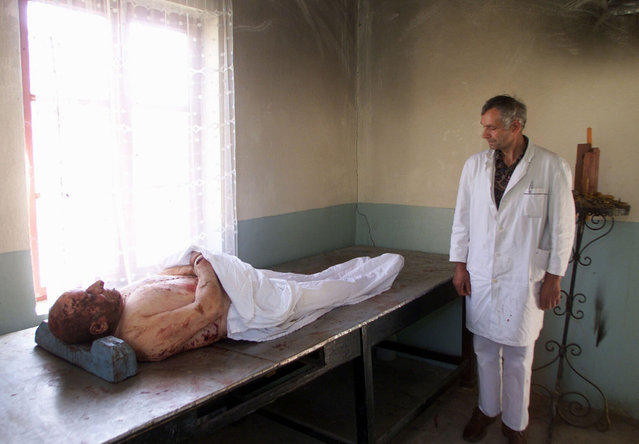 A morgue worker stands beside a man killed during NATO air raids over the town of Aleksinac, south of Belgrade, May 1999. (Photo by Desmond Boylan/Reuters)