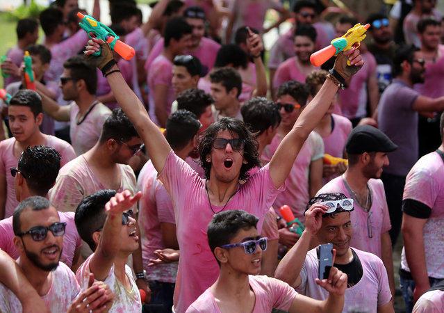 "Iraqi youths holding water guns take part in the ""Festival of Colours"" organised in Baghdad on April 10, 2015, in support of Iraqi troops and Popular Mobilisation Units fighting against the Islamic State (IS) group. (Photo by Ahmad Al-Rubaye/AFP Photo)"