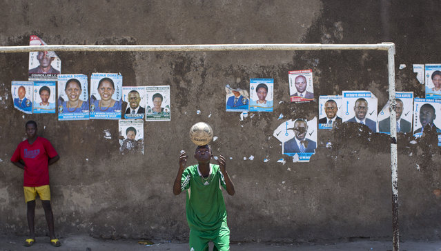 Boys play football and practice balancing tricks in front of a wall plastered with campaign posters for opposition leader Kizza Besigye, as well as for local members of Parliament, in a poor market area of the capital Kampala, Uganda Wednesday, February 17, 2016. (Photo by Ben Curtis/AP Photo)
