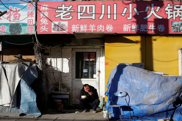 A man has a meal at Shigezhuang village, where many migrant workers living there have left for their hometowns ahead of the Chinese Lunar New Year, in Beijing, China, January 13, 2017. (Photo by Jason Lee/Reuters)