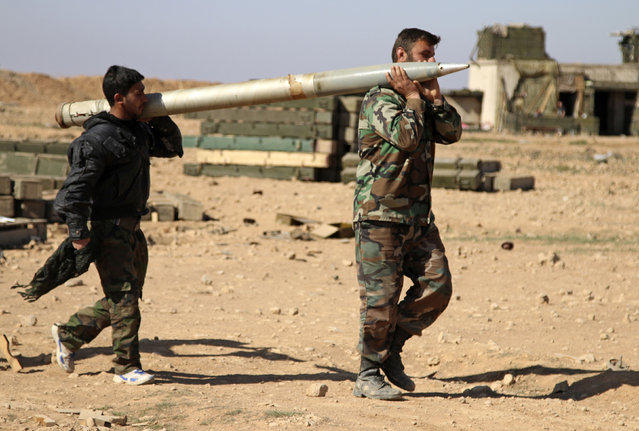 In this photo taken on Wednesday, February 17, 2016, soldiers from the Syrian army carry a rocket to fire at Islamic State group positions in the province of Raqqa, Syria. (Photo by Alexander Kots/Komsomolskaya Pravda via AP Photo)