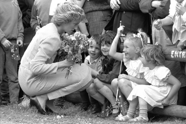 """In this file photo dated February 11, 1985, Britain's Princess Diana stoops to speak to children during a visit to Macedon, Australia. For someone who began her life in the spotlight as """"Shy Di"""", Princess Diana became an unlikely, revolutionary during her years in the House of Windsor. She helped modernize the monarchy by making it more personal, changing the way the royal family related to people. By interacting more intimately with the public – kneeling to the level of children, sitting on edge of a patient's hospital bed, writing personal notes to her fans – she set an example that has been followed by other royals as the monarchy worked to become more human and remain relevant in the 21st century. (Photo by Jim Bourdier/AP Photo/File)"""
