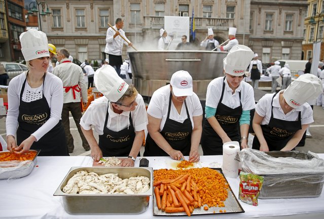 """Bosnian chefs cook in a Guinness Book of World Records attempt for the largest chicken broth, in a central square of the Bosnian capital of Sarajevo, April 17, 2015. """"Bey's Broth"""", the Bosnian meat and vegetable speciality weighing 4,124 kilograms, was cooked in a 2.5 metre diameter pot specially made by a local company. (Photo by Dado Ruvic/Reuters)"""